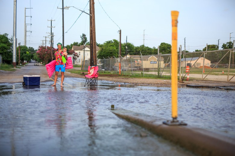 A Dignowity Hill resident brings his baby to cool off on a warm summer night. Photo by Scott Ball