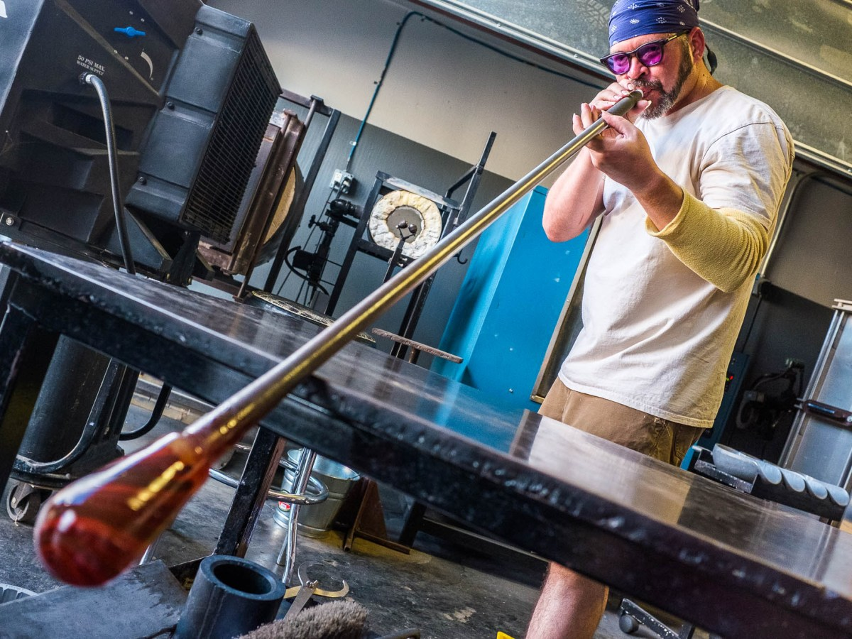Len Andrews II blows through the metal tube expanding malleable glass. Photo by Scott Ball.