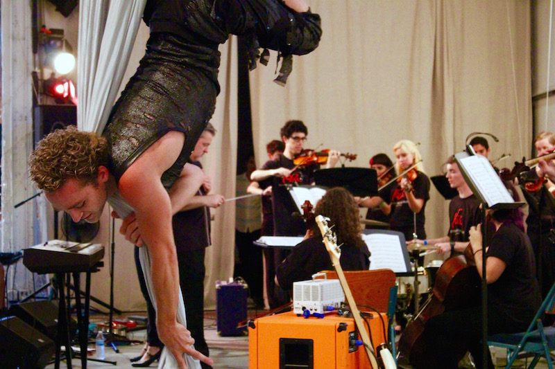 Aerial acrobatics performer, Daniel Patrick, accompanies the YOSA orchestra. Photo by Hagen Meyer.