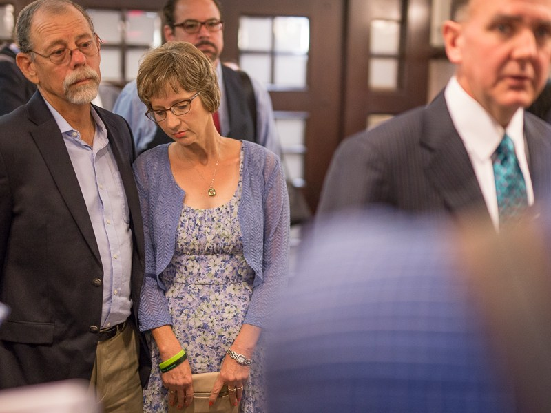 Cameron's parents Mickey (left) and Valerie Redus look on as their attorney Brent Perry (right) speaks to reporters. Photo by Scott Ball.