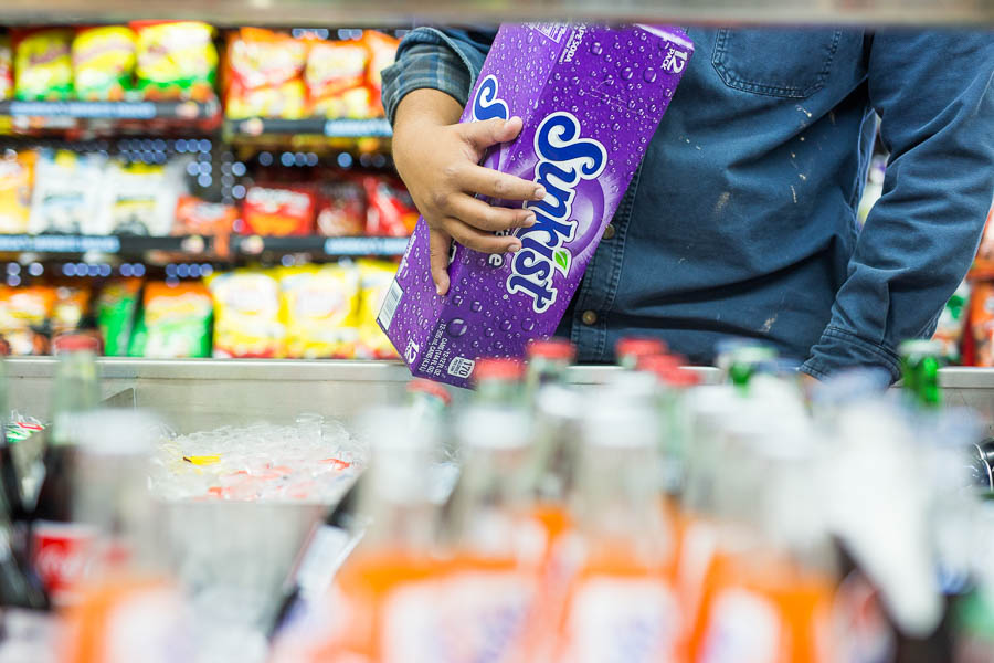 A gas station worker stocks grape soda in a display case. Overconsumption of sugary drinks are a major contributor to adult and adolescent obesity in Bexar County. Photo by Scott Ball