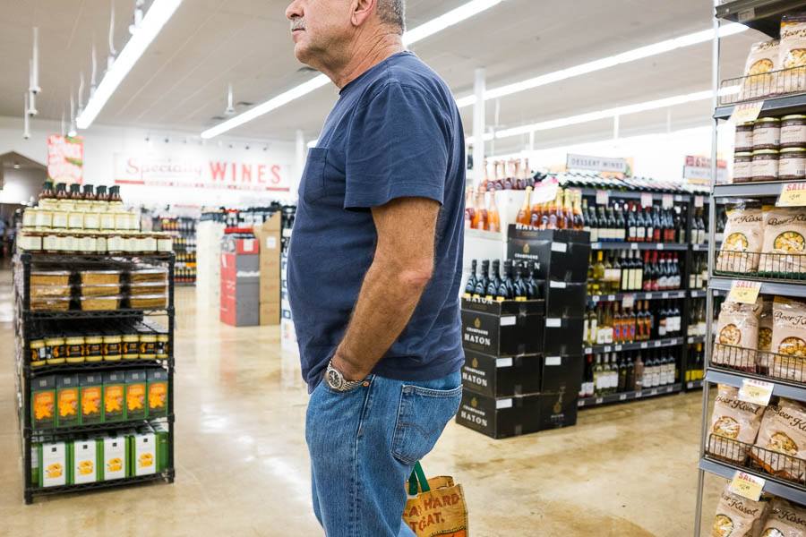 A customer at Central Market stands in-between aisles while making his selections. Photo by Scott Ball.