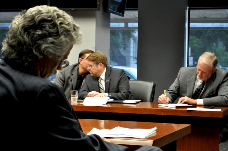 Jeff Londa, the City's lead negotiator (left), reads over his latest proposal to the police union's lead negotiator Ron DeLord (right) while SAPOA Vice President Dean Fischer (center, left) whispers into President Mike Helle's ear. Photo by Iris Dimmick.
