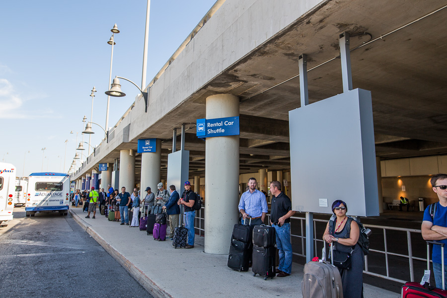 Travelers stand outside Terminal A where the work is hung waiting for shuttles. Photo by Scott Ball.