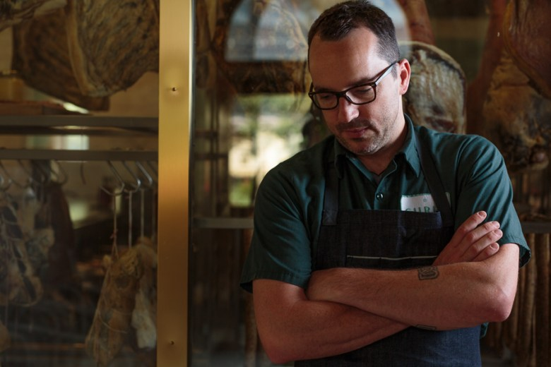 Chef Steve McHugh stands in front of a selection of cured meats. Photo by Scott Ball.