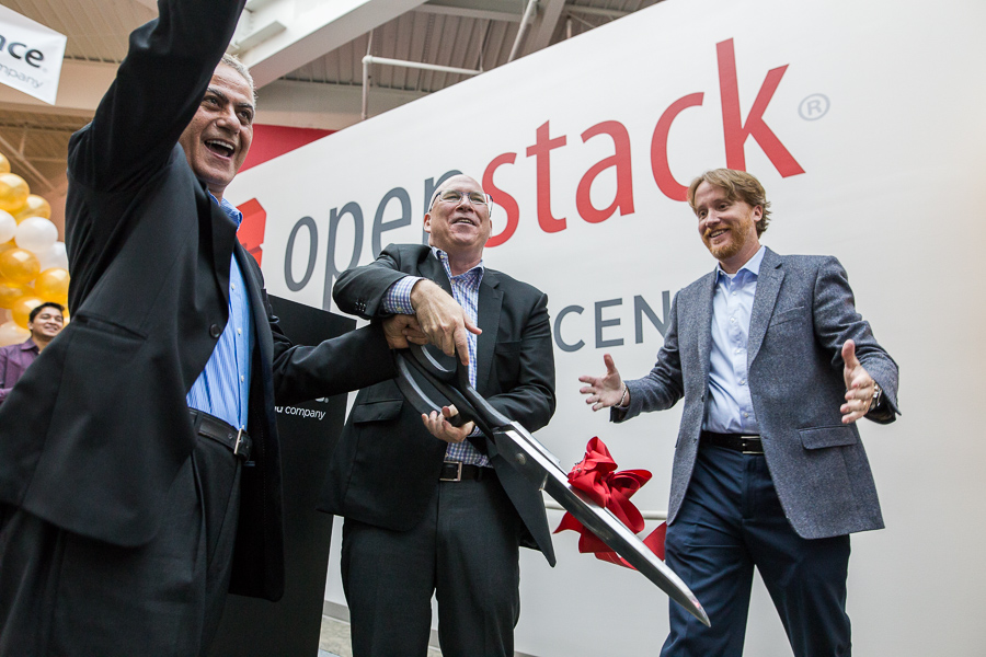 Scott Crenshaw (middle) gets help from Imad Sousou, and Darrin Hanson on the ribbon cutting of the OpenStack Innovation Center. Photo by Scott Ball.