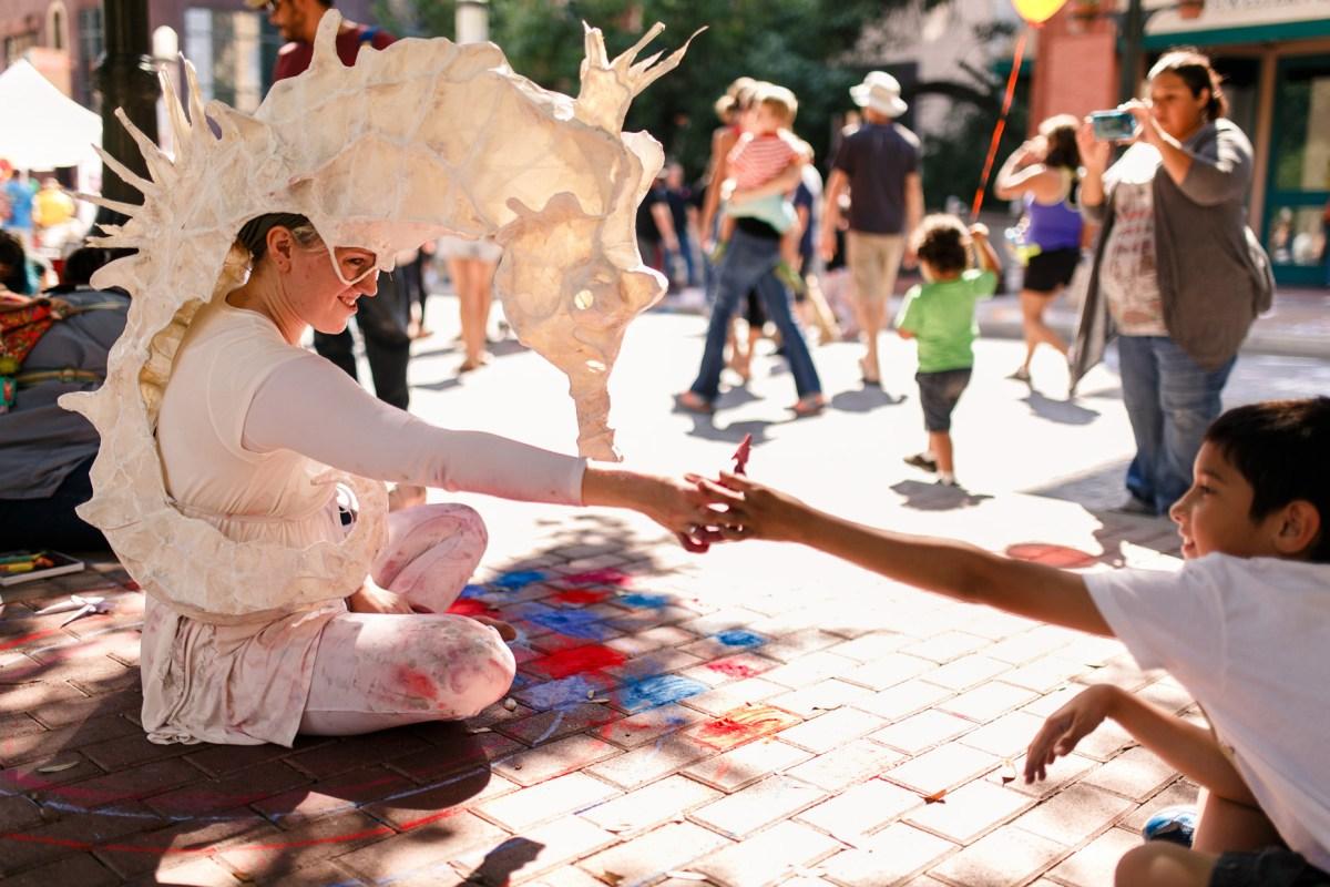 Feature artist, Sarah Fox, passes a piece of art to a boy during Artpace's Chalk it Up 2015. (Photo: Josh Huskin)