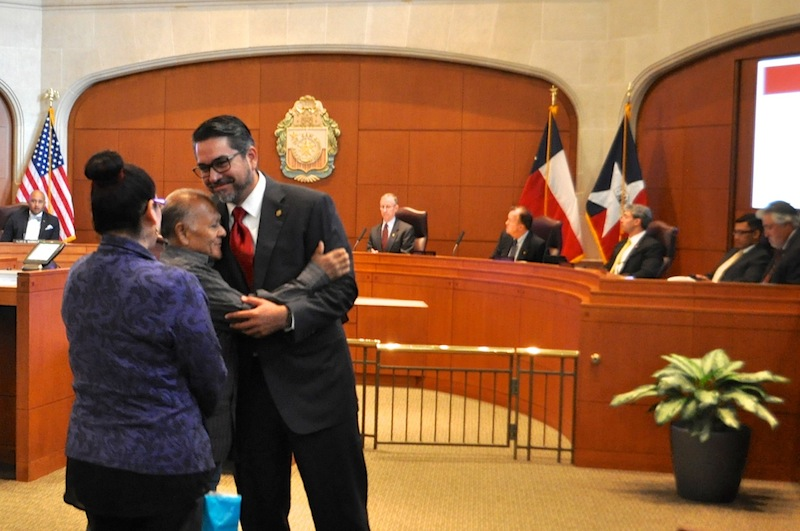Miguel Calzada (center) hugs Councilmember Roberto Treviño (D1) in City Council Chambers while his daughter, Anabel (left), looks on. Photo by Iris Dimmick.