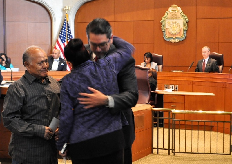 Anabel Calzada (center) hugs Councilmember Roberto Treviño (D1) in City Council Chambers while her father, Miguel (left), looks on. Photo by Iris Dimmick.
