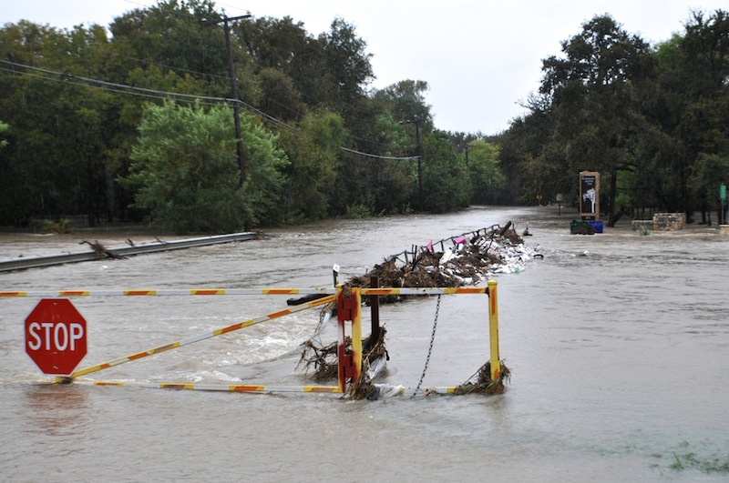 Trash is caught by a guardrail on a flooded Jones Maltsberger Road. Photo by Iris Dimmick.