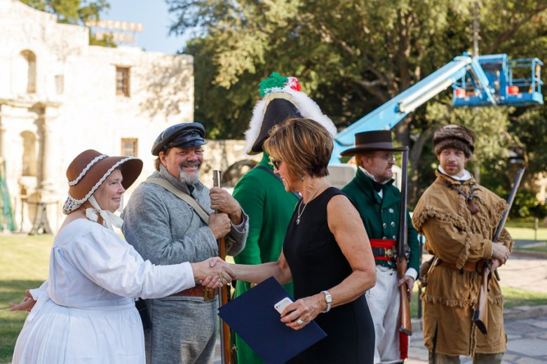 San Antonio City Manager Sheryl Sculley shakes hands with Alamo reenactor's. Photo by Scott Ball.