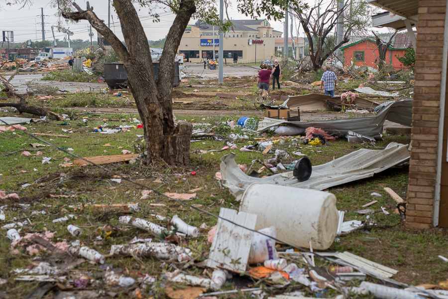 Courtney Chilek looks out her bathroom window where her and her children were taking shelter when the tornado touched down near her house. Photo by Scott Ball.
