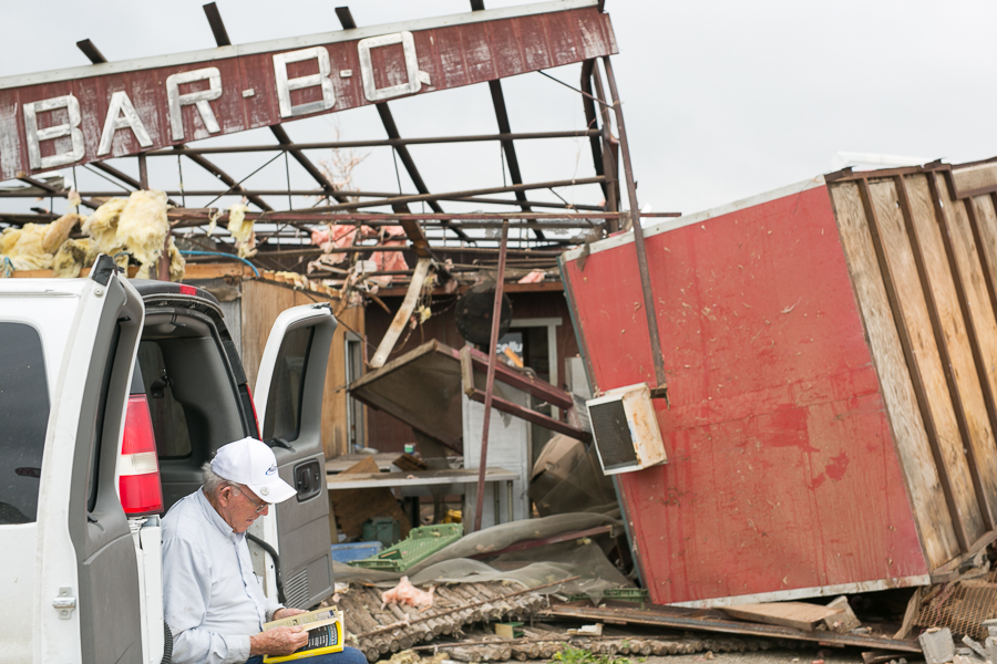 An owner of Lazy J Bar-B-Q looks through the yellow pages after his business is destroyed. Photo by Scott Ball.
