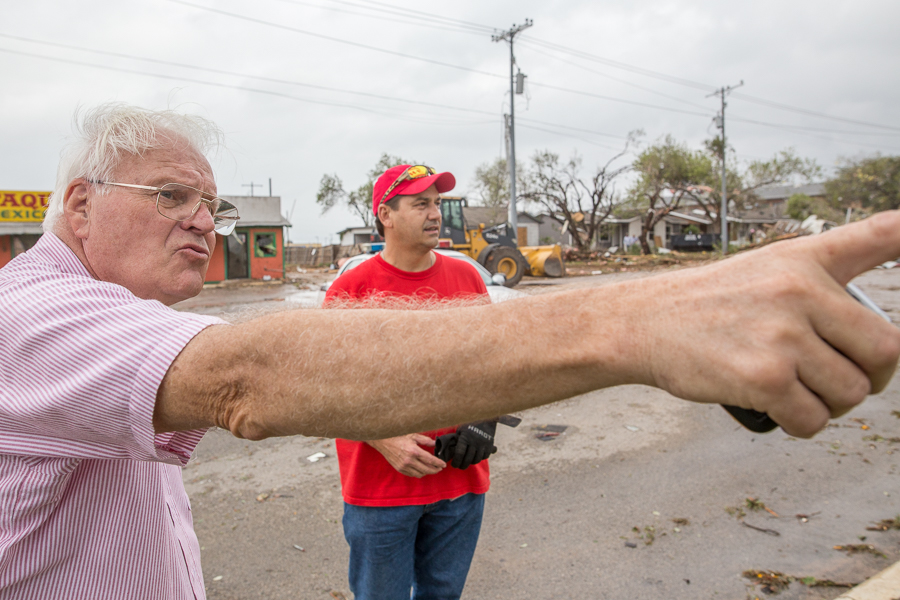 Floresville ISD bus driver Martin Peterrsson (left) points at damage down the road as HEB employee Sheldon Kotara looks on. Photo by Scott Ball.