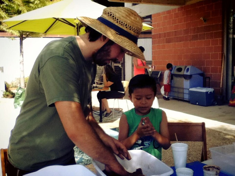 Alexander Gonzalez helps a child make a seed ball during Síclovía. Photo courtesy of TBG.