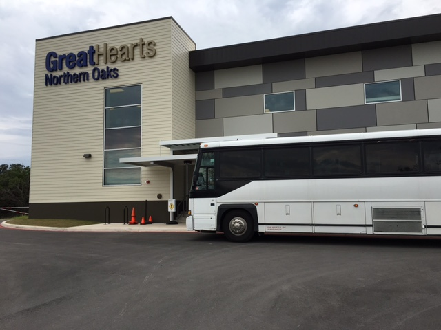 A bus full of elected leaders and staff rolls up to Great Hearts Northern Oaks. Photo by Bekah McNeel