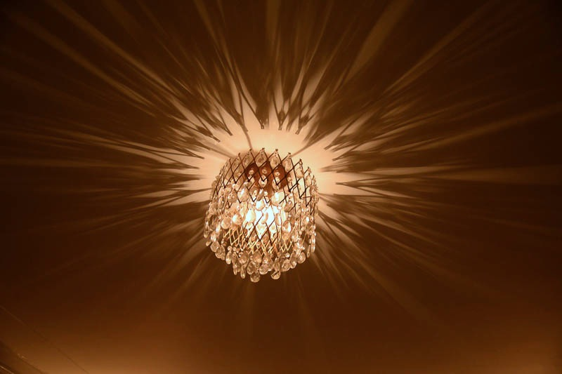 A light casts a star-like pattern of the ceiling in a hallway at the St. Anthony Hotel. Photo by Annette Crawford.