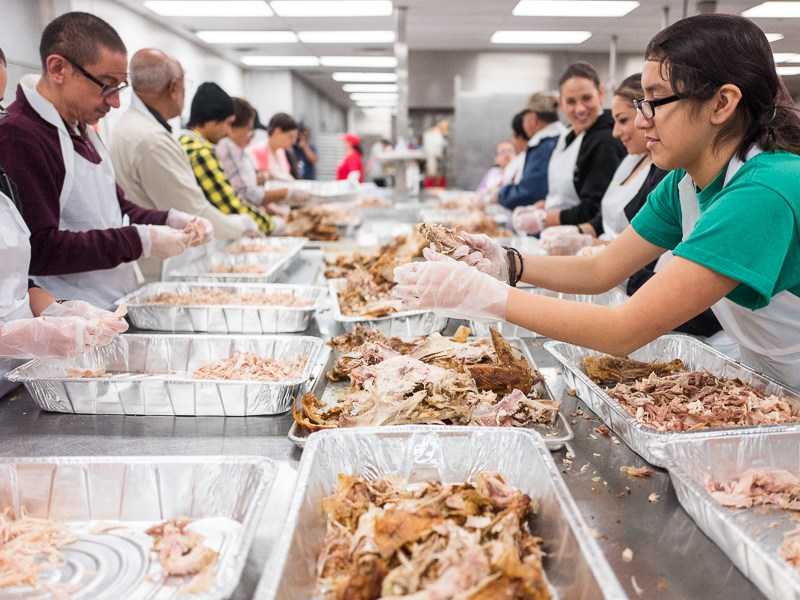 An assembly line of volunteers separate the white meat from the dark meat on large prep tables. Photo by Scott Ball.
