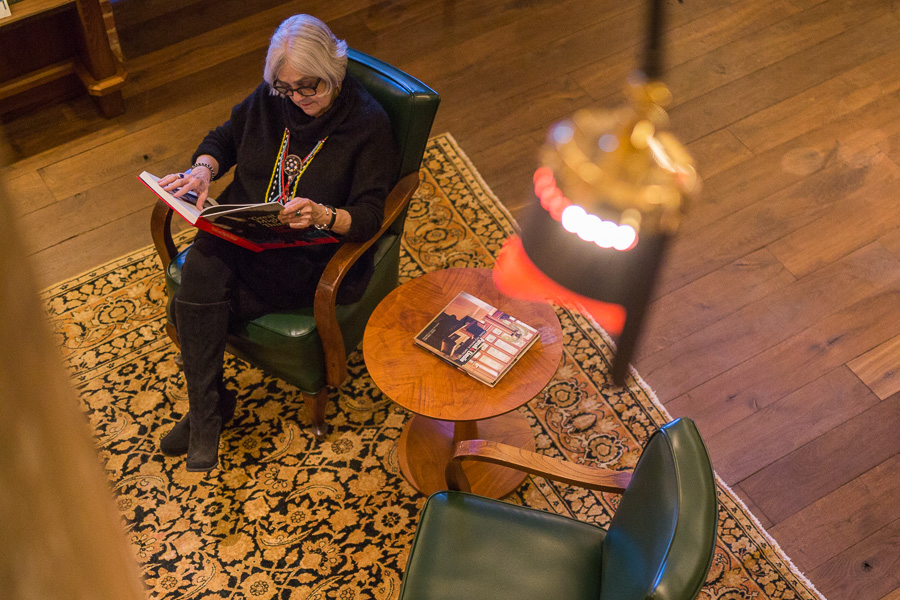 Sherry Kafka Wagner reads a book from her collection at Hotel Emma. Photo by Scott Ball.