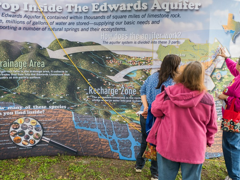 Interested festival attendees take a closer look at en educational Edwards Aquifer display. Photo by Scott Ball.