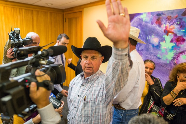 Burleson County resident Gabbo Goetsch raises his hand to stop the chanting so they can talk with a city official. Photo by Scott Ball.