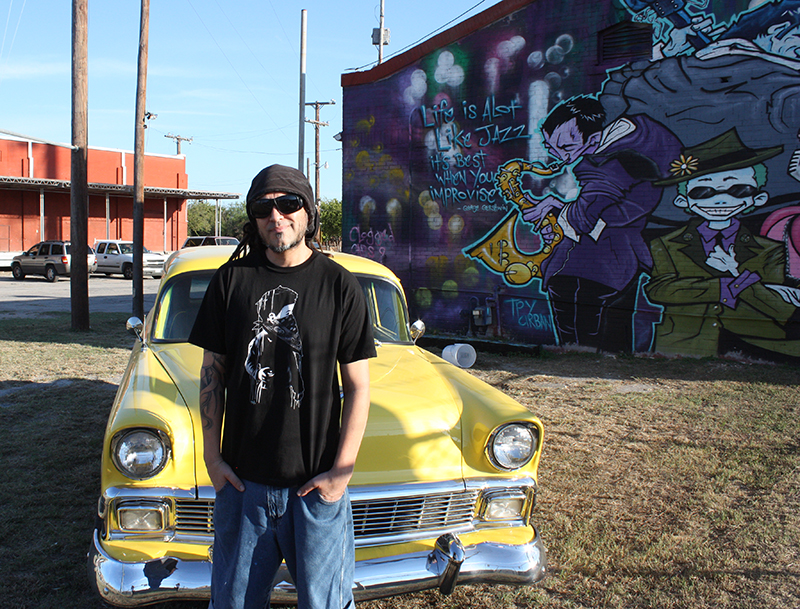 Nik Soupe poses for a photo next to his jazz inspired mural that he completed in April of 2014. Photo by Kay Richter.