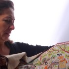 Floriana Venetico, SHE representative, holds up an intricate Kantha textile that shows a village life scene. Photo by Abbey Francis.