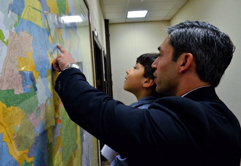 Councilman Ron Nirenberg (D8) shows his son, Jonah, a map of San Antonio in City Hall. Photo by Jonathan Alonzo.