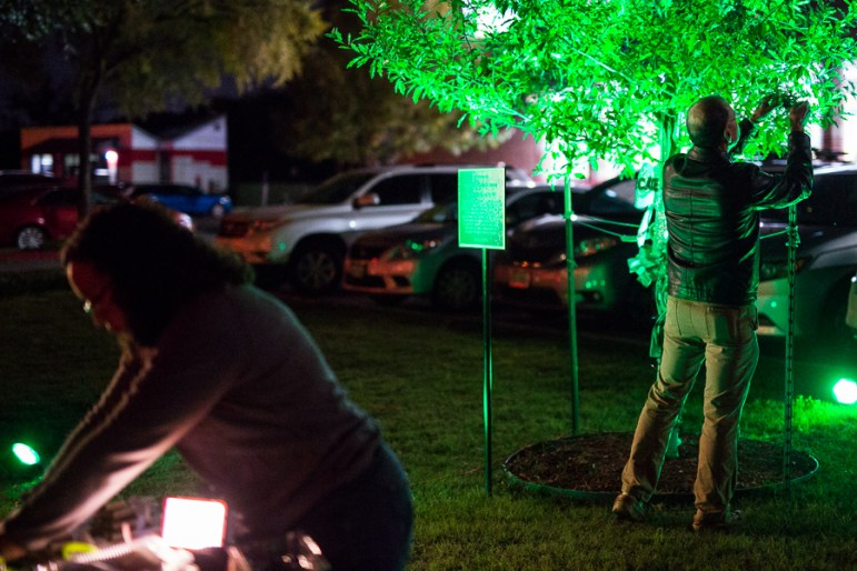 Mickey Redus hangs a wristband around the tree dedicated in his sons honor. Photo by Scott Ball.