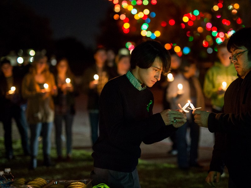 Friend of Cameron Redus and organizer of the event Jonathan Guajardo lights his candle. Photo by Scott Ball.
