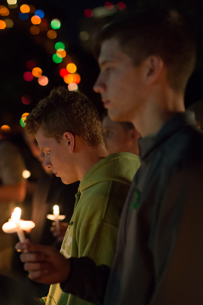 Ethan (left) and William Redus hold candles during the second anniversary of their brothers death. Photo by Scott Ball.