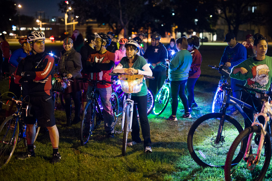 Trish Rubio (center) waits at Maverick Park with fellow cyclists as the packages are prepared to be delivered. Photo by Scott Ball.