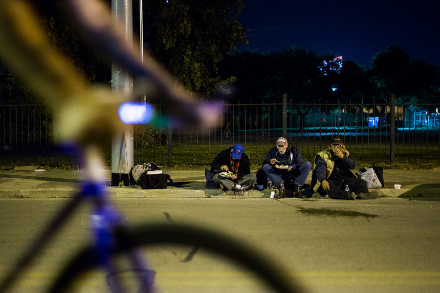 A cyclist passes by while dinner is served from The Chow Train. Photo by Scott Ball.