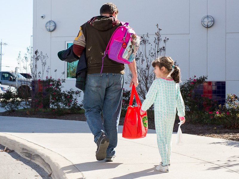A father and daughter walk to their vehicle with a bag of produce. Photo by Scott Ball.