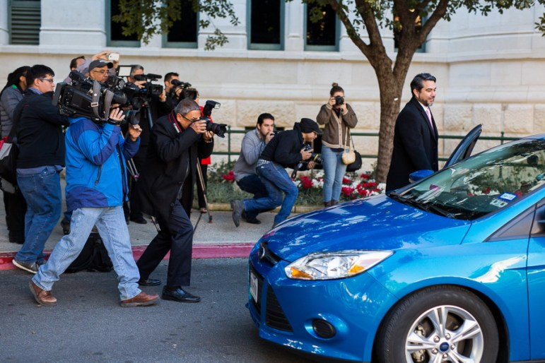 Reporters surround the Lyft vehicle as Councilman Roberto Treviño (D1) opens the door for Mayor Ivy Taylor. Photo by Scott Ball.