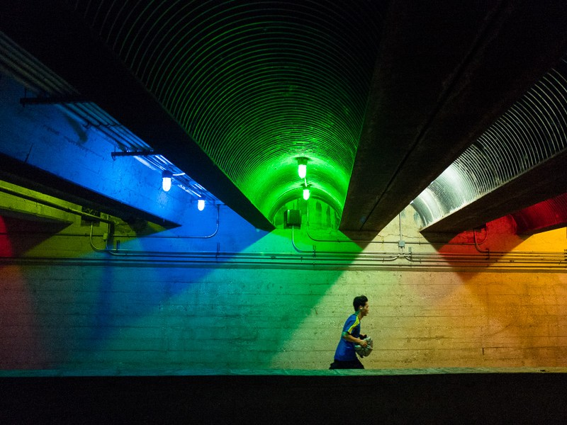 A jogger runs underneath the Jones Street bridge which has been decorated with holiday lights. Photo by Scott Ball.