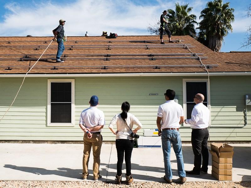 Carlos Abad, Fanny Reyes, Supratim Srinivasan, and Eduardo Casilda look on as Luis Medellin works on the roof. Photo by Scott Ball.