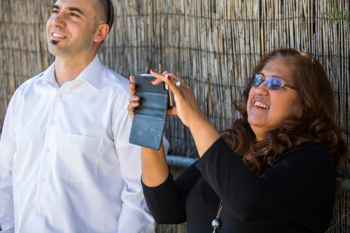 Myra Garcia takes a photograph of her house as it is prepared for solar panels as KACO New Energy Director of Sales Eduardo Casilda looks on. Photo by Scott Ball.