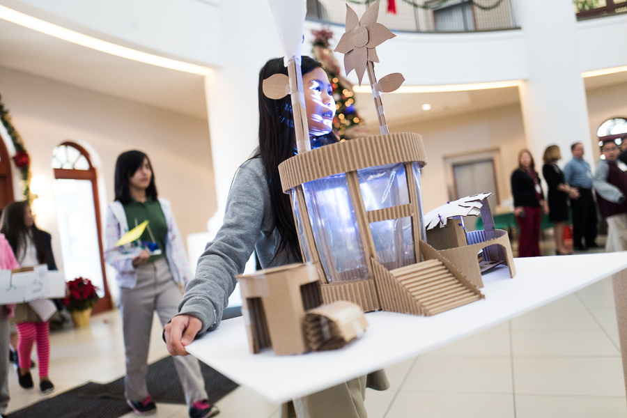 A student brings in a classroom designed bus stop made out of cardboard and plastic. Photo by Scott Ball.
