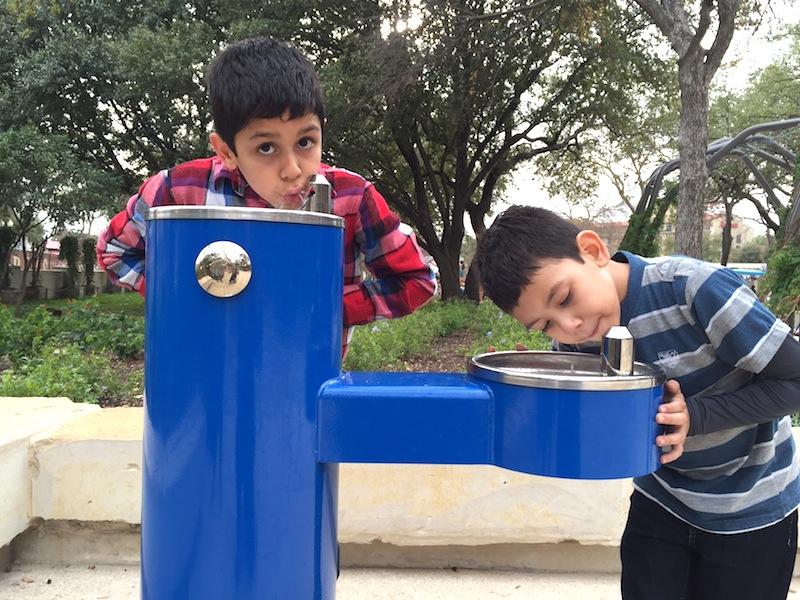 Osvaldo Aguirre, 9, of El Paso and his cousin André Espinoza, 7, of Laredo take a water break in Yanaguana Garden. Photo by Robert Rivard.