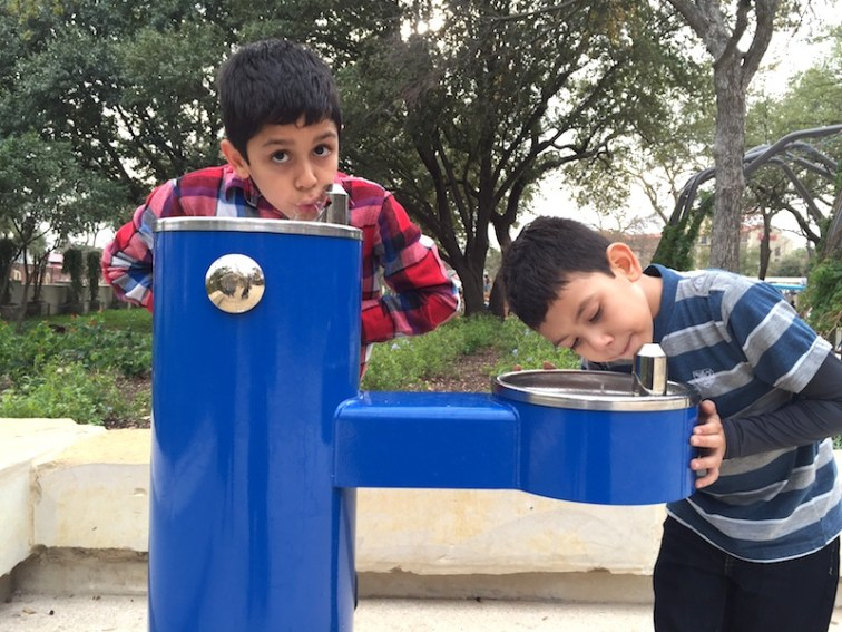 Osvaldo Aguirre, 9, of El Paso and his cousin André Espinoza, 7, of Laredo take a water break in Yanaguana Garden. Photo by Robert Rivard.