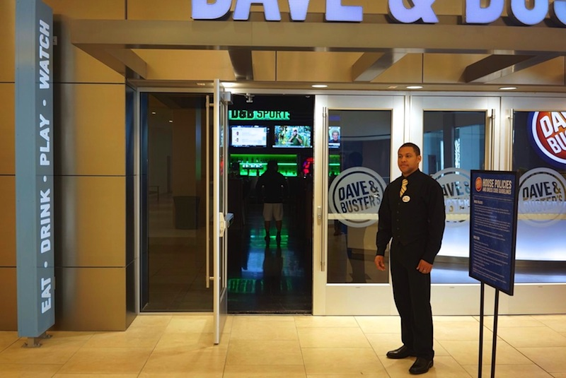 """Zachary Bayerl, a Dave & Buster's """"captain"""" greets guests, checks I.D.s and generally helps out other staff to make sure things run smoothly, he said. Photo by Iris Dimmick."""