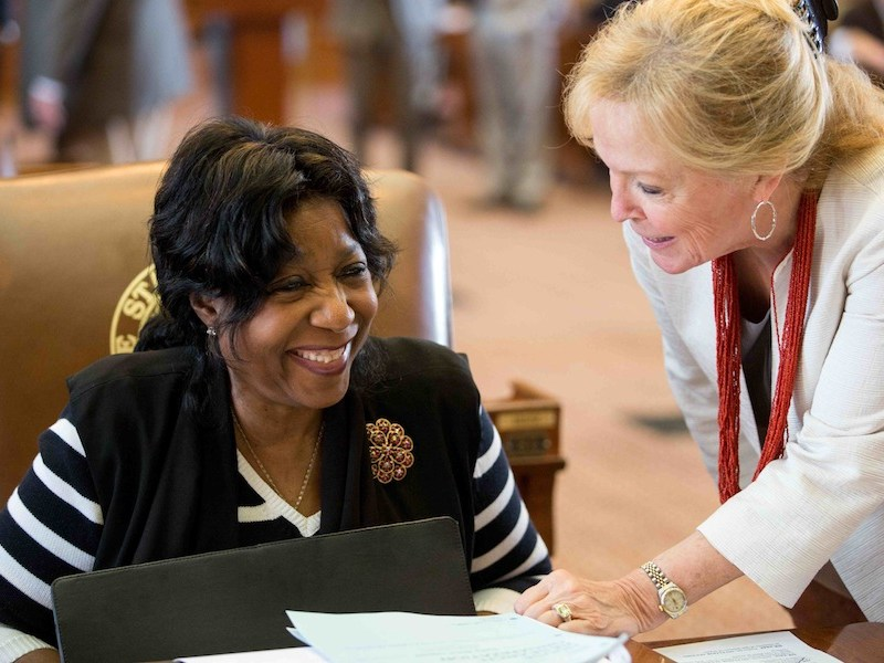 State Rep. Ruth Jones McClendon (left) speaks with state Rep. Myra Crownover on the legislature floor. Photo courtesy of McClendon staff / District 120.