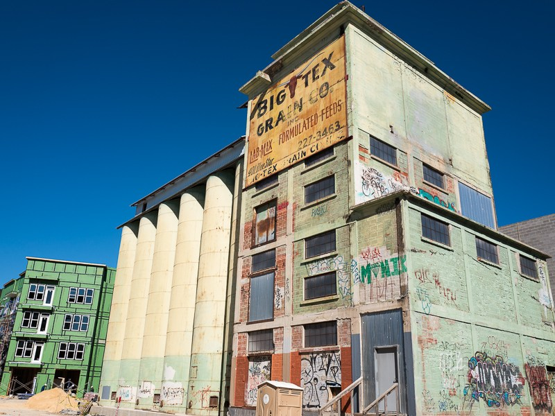 Graffittied and worn, one of the original Big Tex Grain Co. buildings will be incorporated into the mixed use development on the San Antonio River. Photo by Scott Ball.