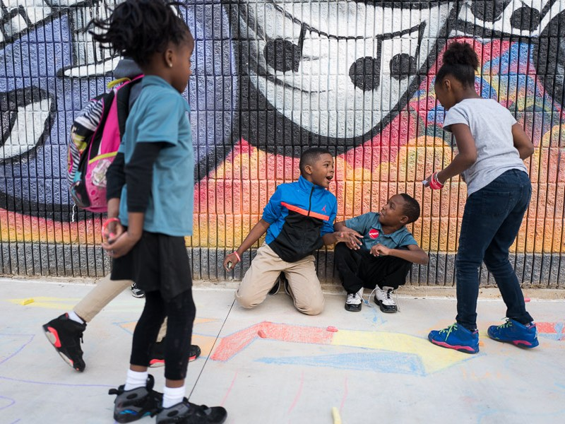 Children play with chalk in front of a mural. Photo by Scott Ball.