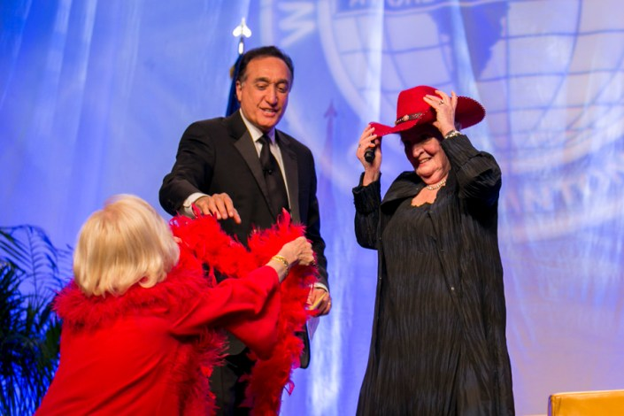 International Citizen of the Year recipient Jane H. Macon gives Madam Secretary her signature red hat and boa. Photo by Kathryn Boyd-Batstone