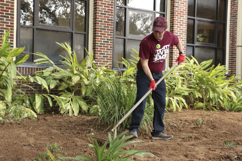 Trinity University President elect, Dr. Danny Anderson tends to the garden in front of Lamar Elementary School as part of the Trinity Gives Back Volunteer Initiative. Photo by Bria Woods.
