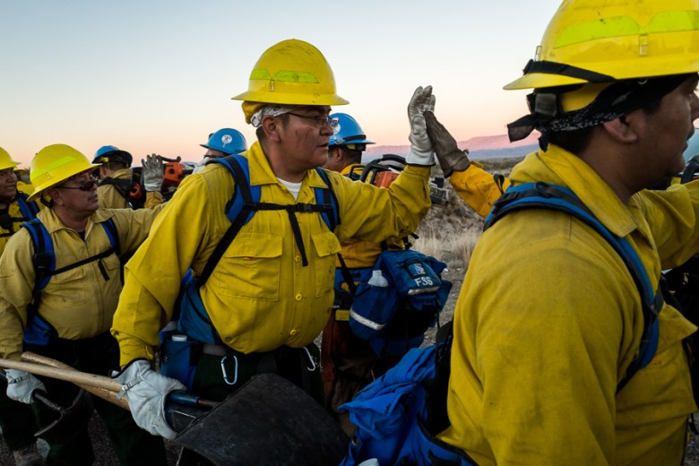 The Indian Affairs Zuni IHC Hotshots high five while giving words of encouragement following a long day fighting fires. Photo by Scott Ball.