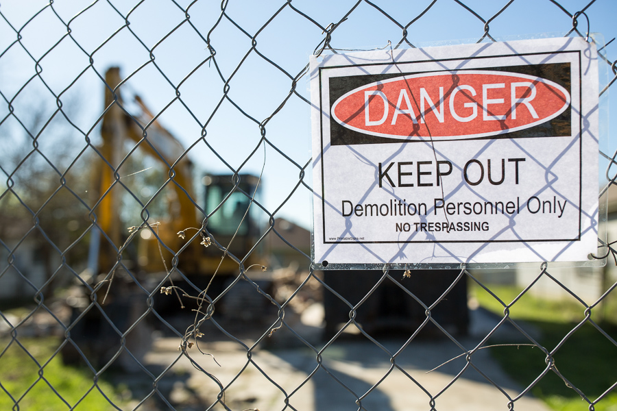 A sign posted on a temporary fence warning those to keep out at one of the two first houses demolished. Photo by Scott Ball.