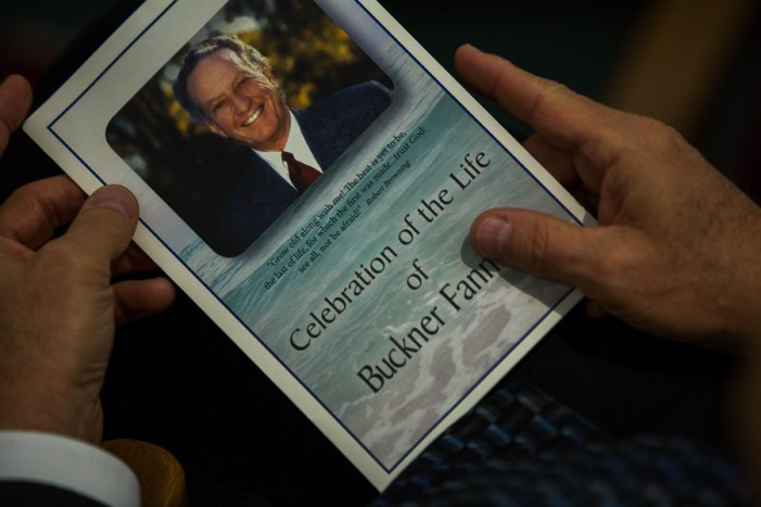 A guest holds a memorial pamphlet celebrating the life of Buckner Fanning. Photo by Scott Ball.